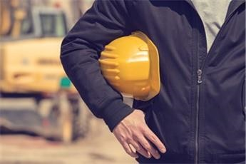 Yellow hard hat underneath a worker's arm