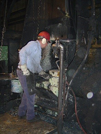 a worker wears hearing protection as he operates heavy machinery