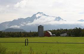large green field with silo and barn in the background, in front of a cloud capped mountain range.