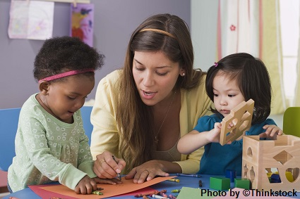A female preschool teacher helps two girls color and construct with building blocks
