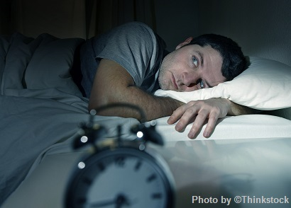Man waking up to alarm clcok in the morning