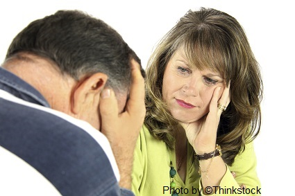 A man with his hands over his face and head down and a woman looks at him with conern