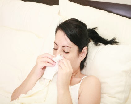 Woman at home sick in bed covering her cough with a tissue.)