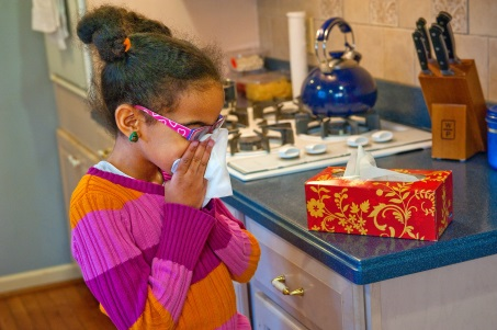 Little girl bloweing her nose with a tissue at home