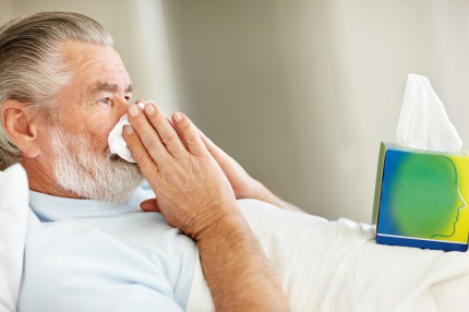 Older man blowing his nose while in bed sick