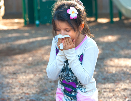 photo of girl blowing her nose with a tissue