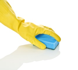 Gloved hand cleaning surface with a sponge.