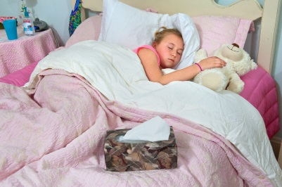 Young girl at home sick in bed.