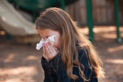 Young girl blowing her nose with a tissue.