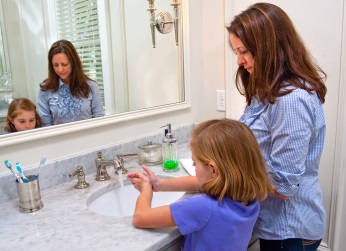 Mother helping her daughter wash her hands in bathroom sink.