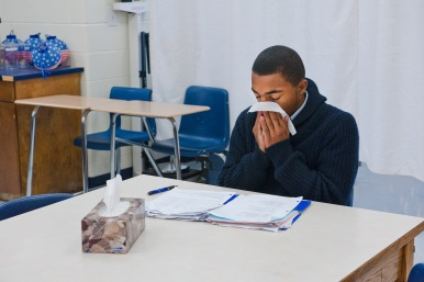 Teen boy at desk in a classroom blowing his nose with a tissue.