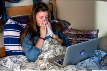 College student blowing her nose with a tissue in bed in her dorm room.