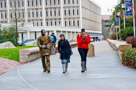 3 college students walking on campus.