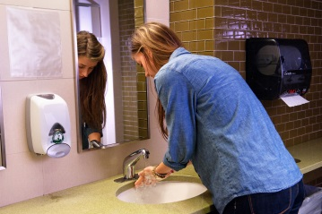 College student washing her hands in the bathroom.