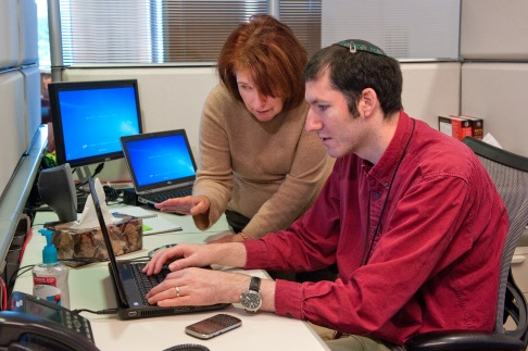 Man and woman at work looking at a computer.