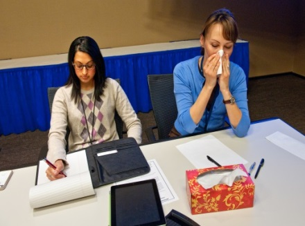 Woman covering her cough with a tissue while sitting beside a co-worker.