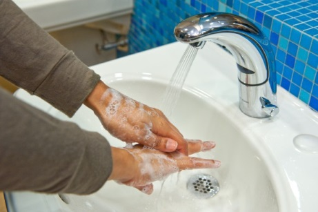 Woman washing her hands with soap and water in a sink at work.
