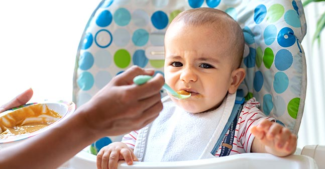 Baby in highchair reacts negatively to baby food.