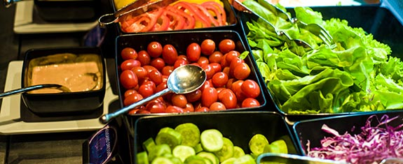 A variety of fresh vegetables on a salad bar