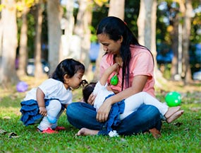 Mom breastfeeding her baby in a park while her toddler kisses the baby's head.