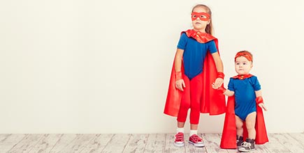 A young girl and her toddler brother in superhero outfits.