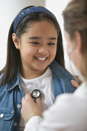 A doctor placing a stethoscope on a girls chest.
