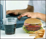 photo of a person at a computer with a hamburger and soda