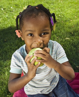 A young girls eating an apple