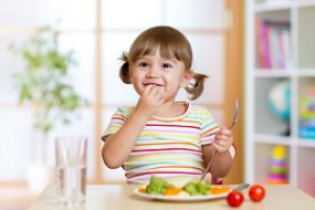 A young girl eating vegetables