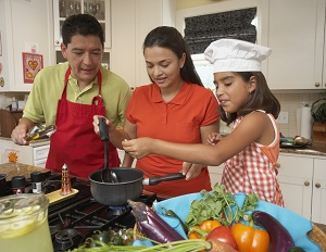 A girl cooking a meal with her parents.