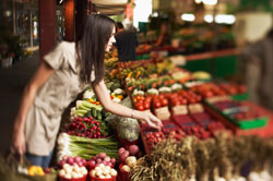 photo of a woman looking at fruits and vegetables in a store