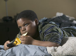 photo of a boy eating chips and watching TV