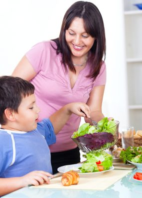 Photo: Mother serving fresh healthy salad to her son