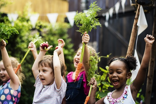 Kids holding carrots in a vegetable garden