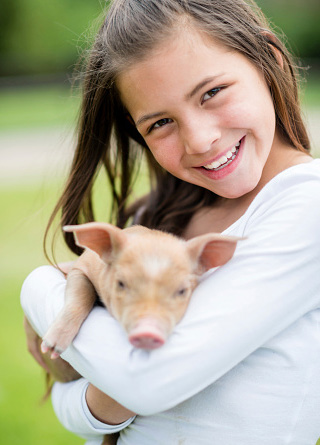 Little girl holding a baby pig