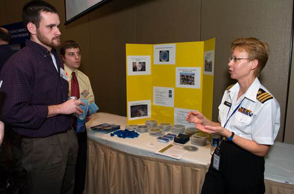 Two students speaking with an instructor at a booth in the exhibit hall