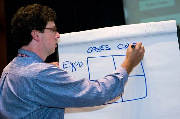 instructor drawing on a board during a basic epidemiology presentation