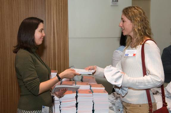 Student receiving an epidemiology book from an instructor
