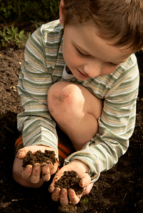 Image of a boy playing with dirt.
