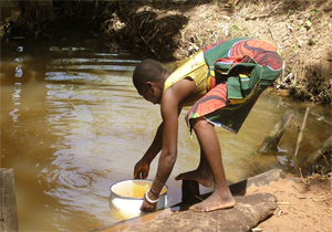 Woman collecting water from a stagnant pool. Photo credit: Emily Staub, 2004, The Carter Center.