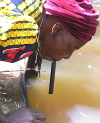 Nigerian woman drinking water directly from a pond through a pipe filter. Photo credit:  Emily Staub, 2002, The Carter Center.
