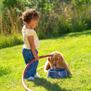 Image of a girl with a dog on a lawn.
