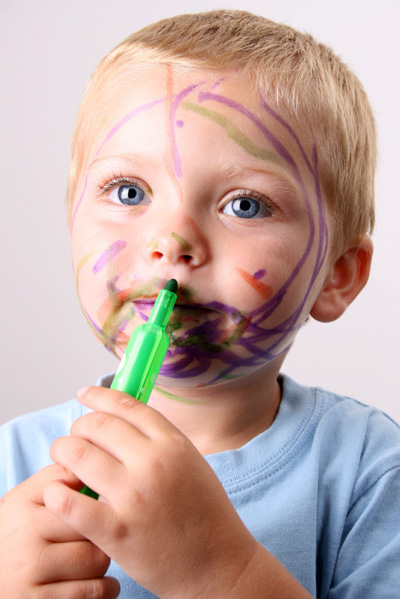 Young boy drawing on his face with a marker
