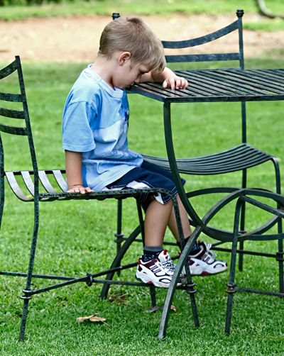 Boy with head down on outside table