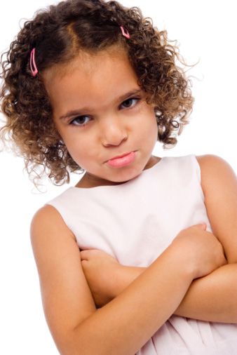 Young girl with curly hair frowning with arms crossed