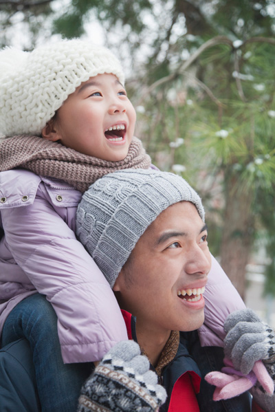 Girl laughing while sitting on dad's shoulders in winter