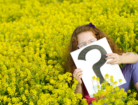 Girl in meadow holding an question mark