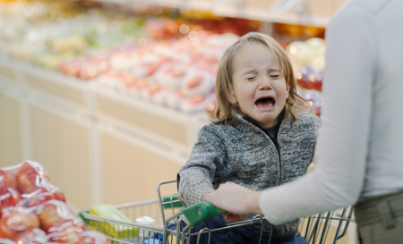 child crying in shopping cart in supermarket