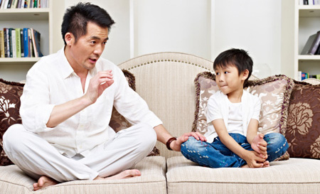 Parent talking to child on couch