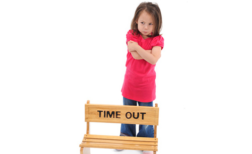 Girl standing in front of time out chair